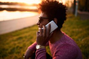 Focus on phone. Young and healthy black man smiling and talking on smart phone in park at sunset