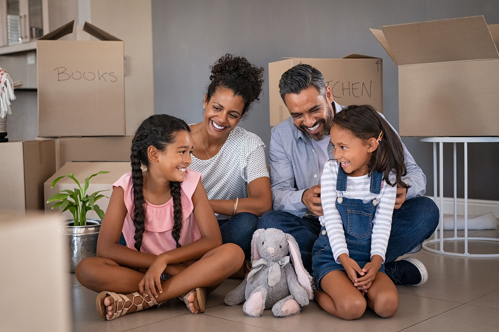 a family smiles with joy as they move into their new home