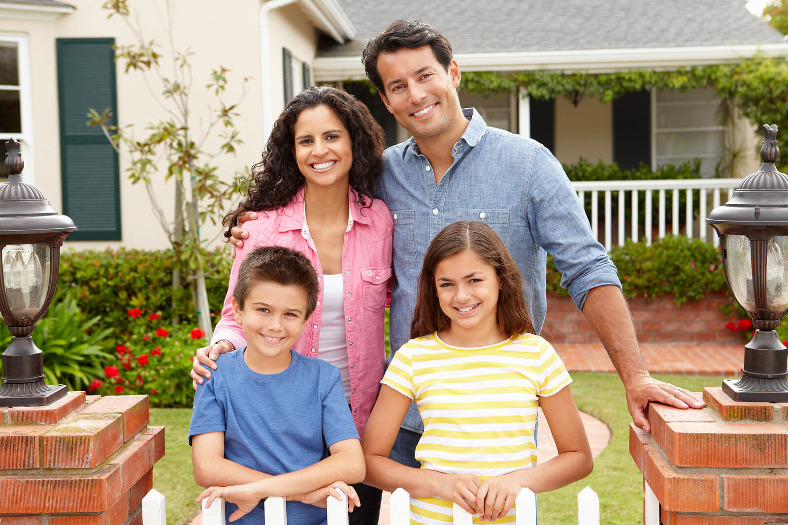 A family stands and smiles in front of their new house