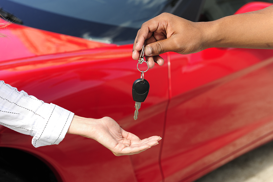 woman's hand receives keys for new car from salesman's hand