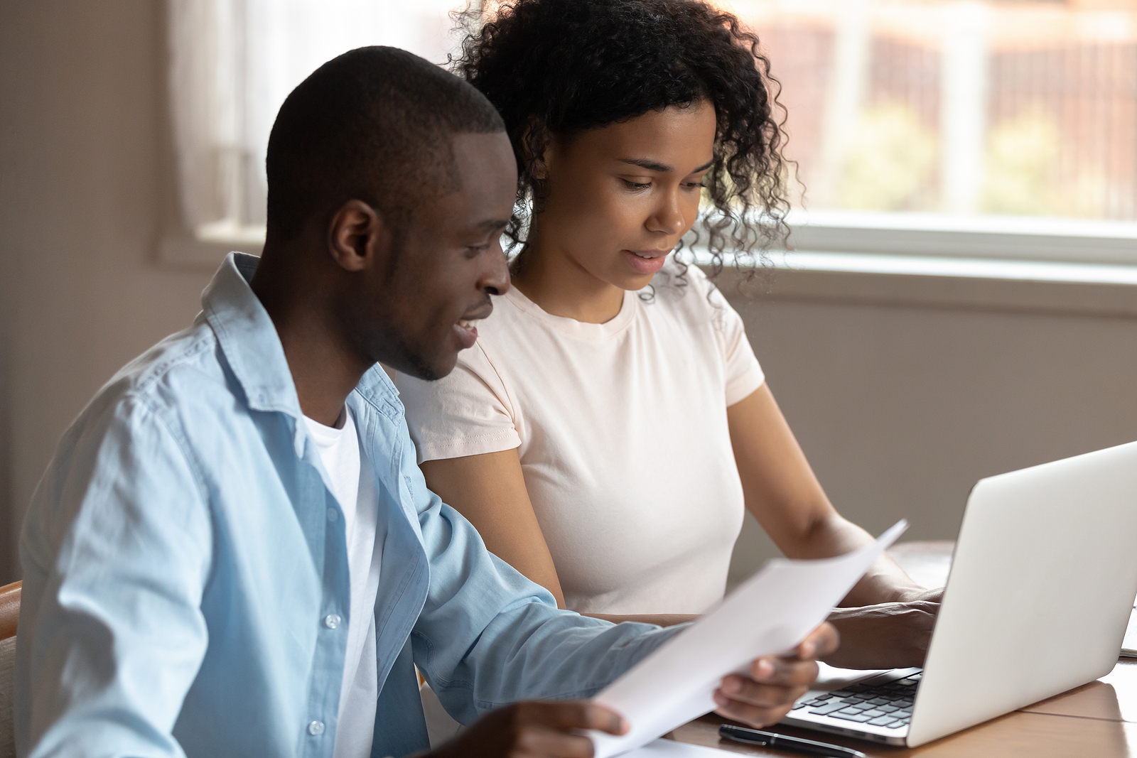 a couple reviews their finances in preparation to get a personal loan online
