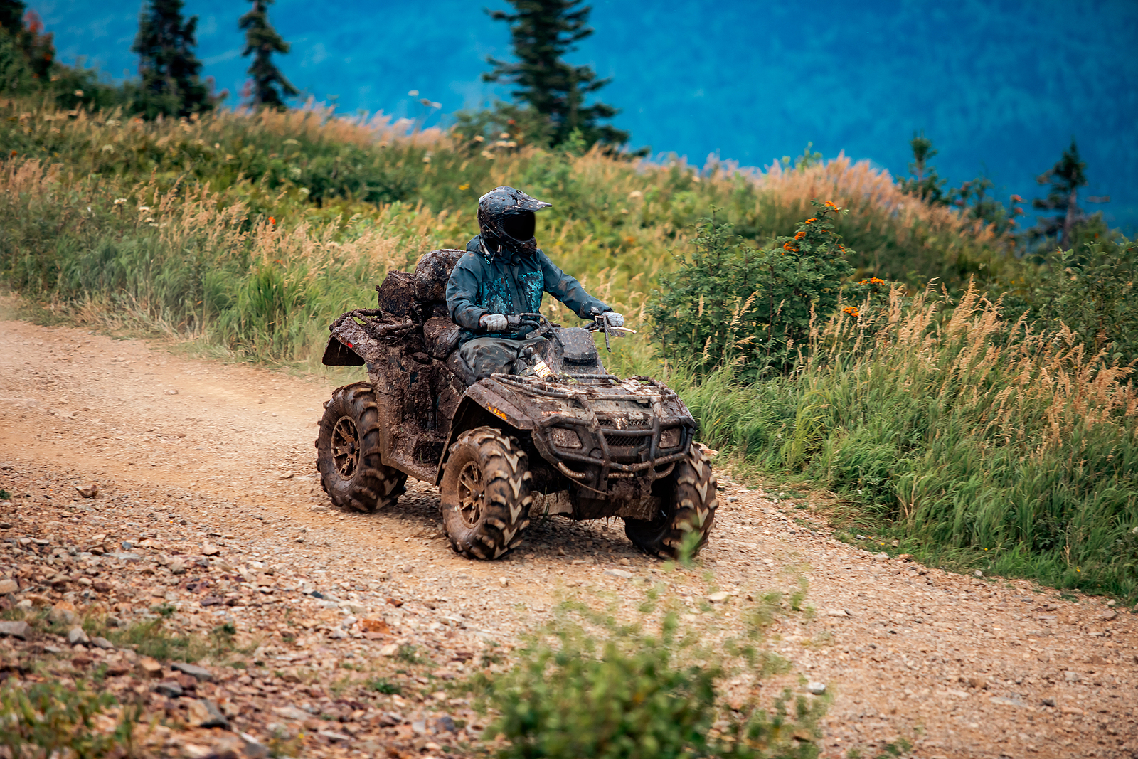 an ATV rider is riding on a dirt trail wearing a helmet.