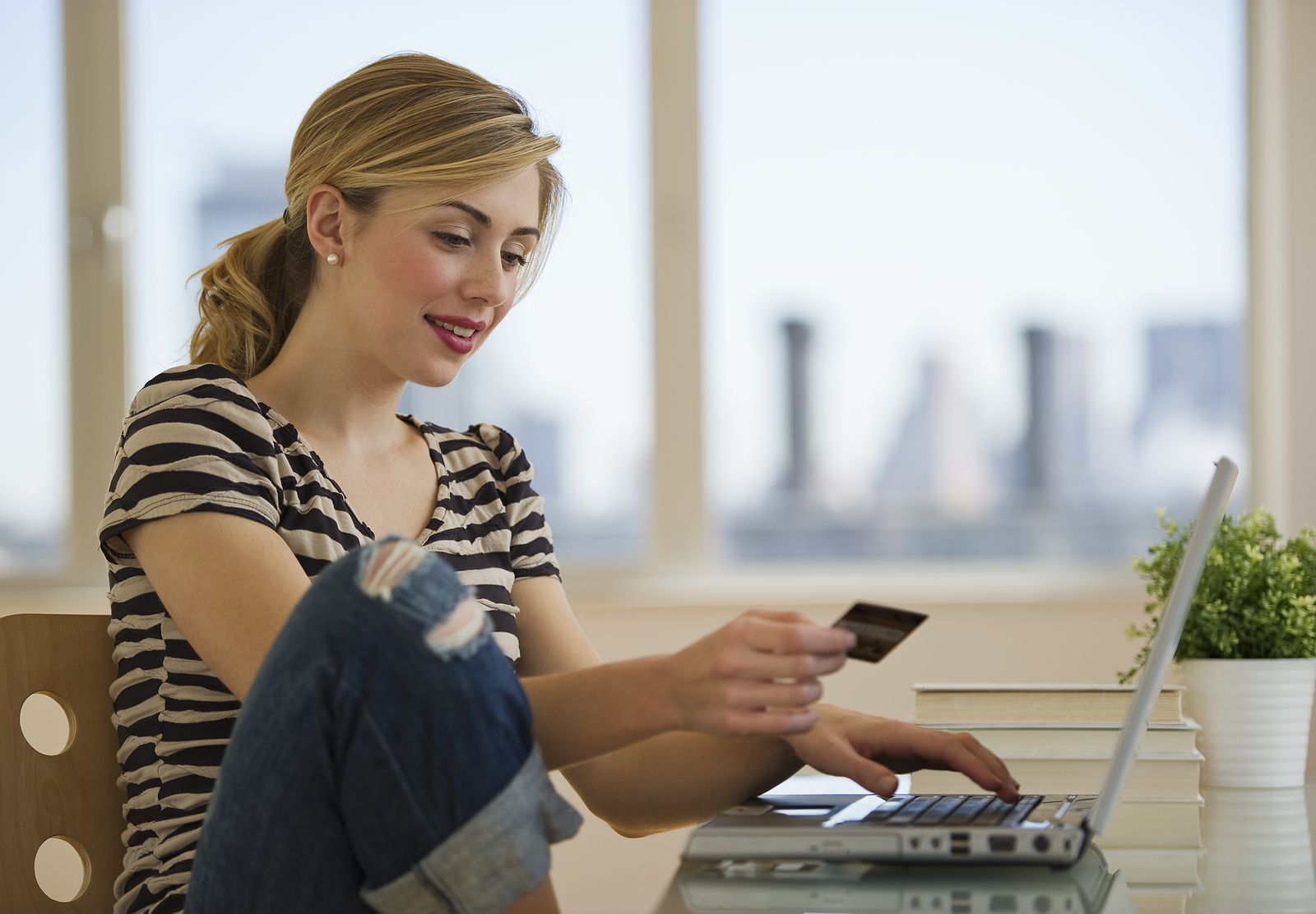 a young woman buys something online with her credit card.