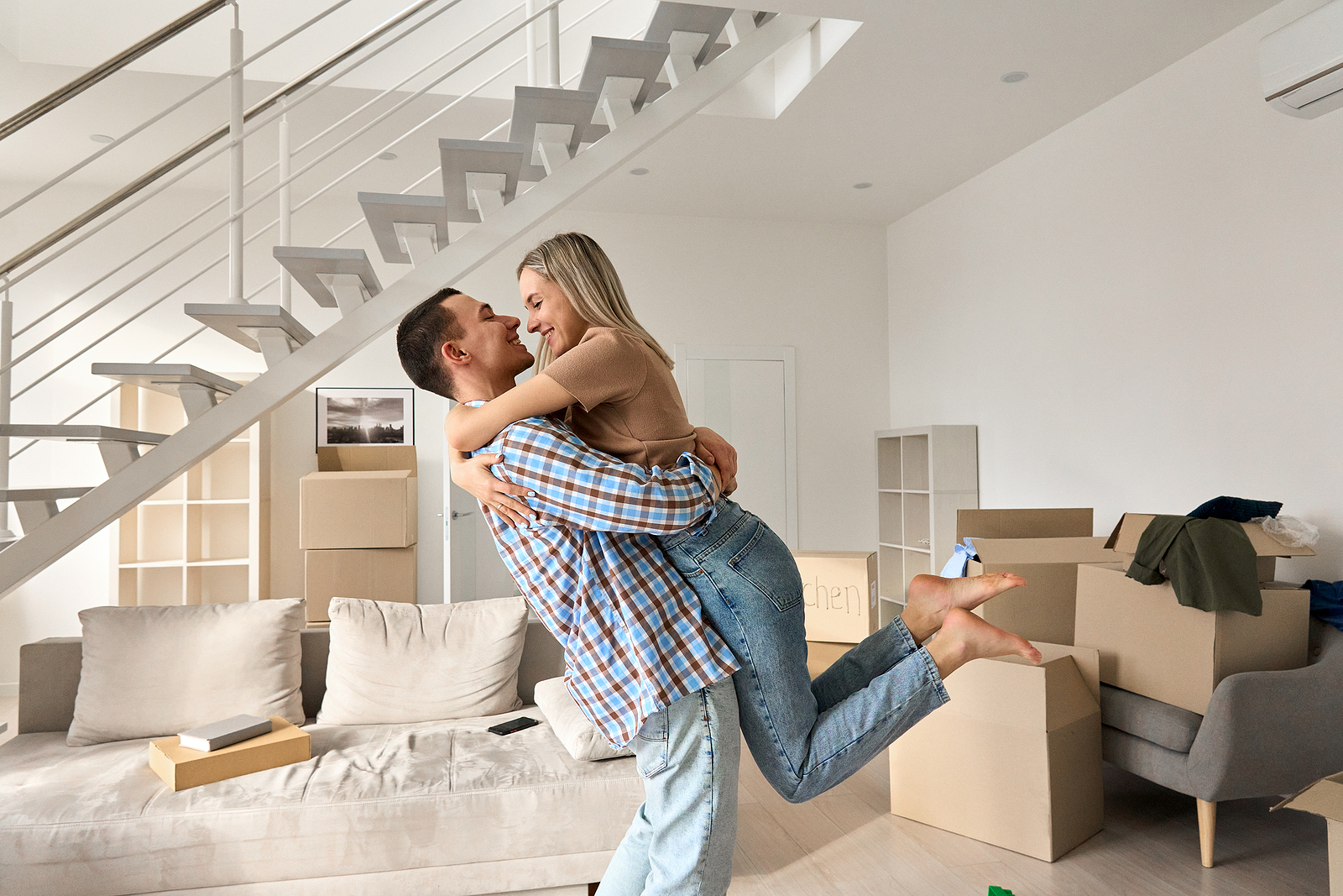 a happy couple surrounded by boxes, hug each other on their moving day.