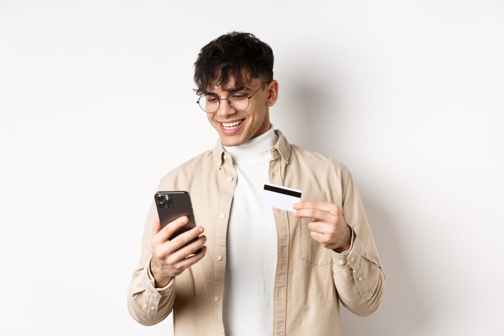 Happy young man using smartphone to make purchases with his new credit card.