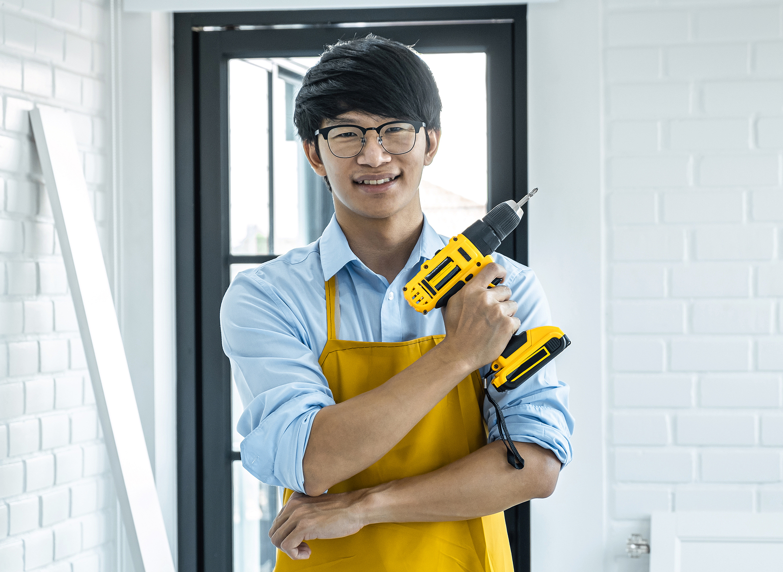 a young man hold a drill as he begins a home improvement project.
