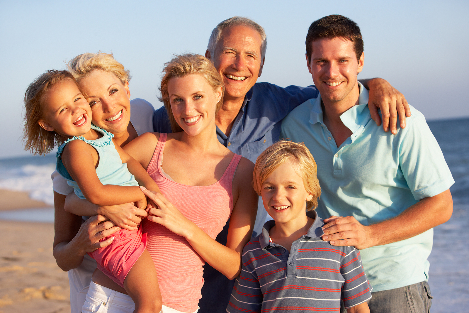 a happy family of parents, grandparents, and children are on the beach on vacation.