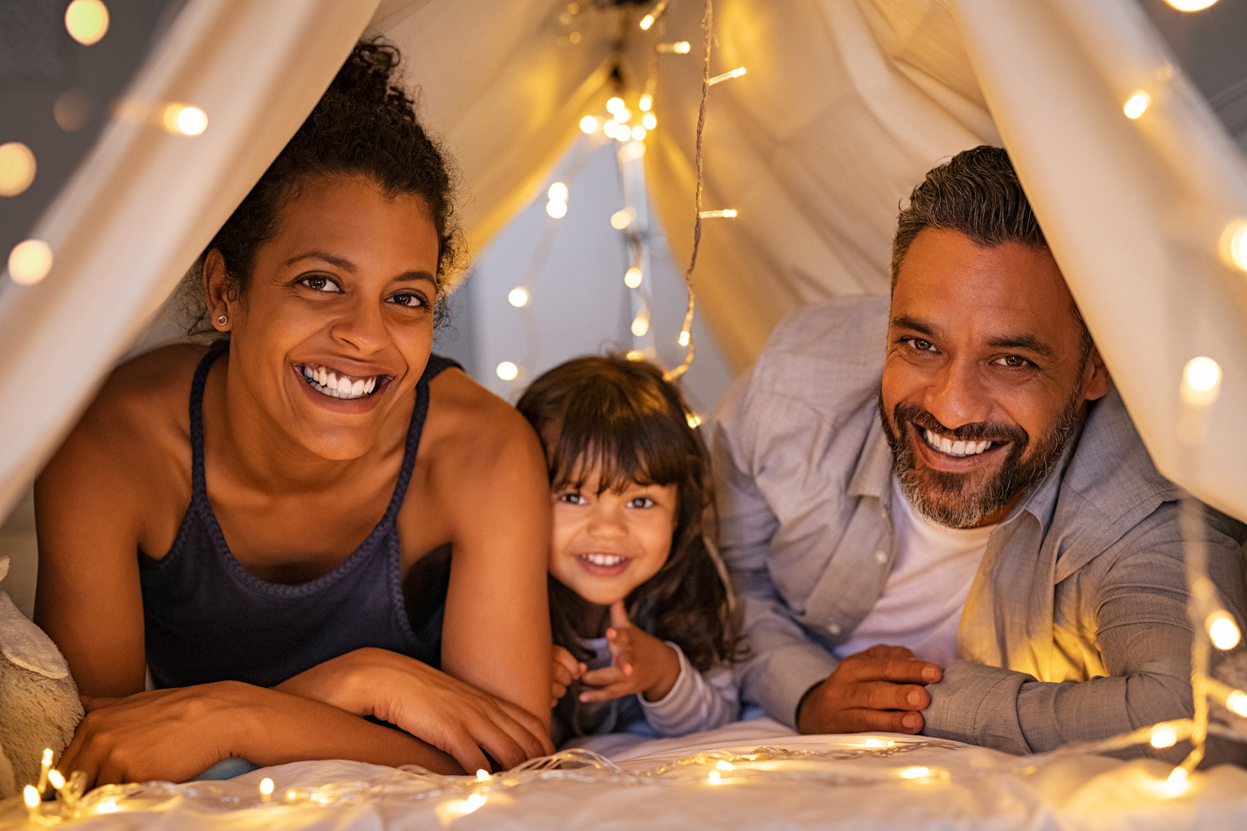 a happy mom and dad lay smiling with their daughter in a tent with fairy lights.