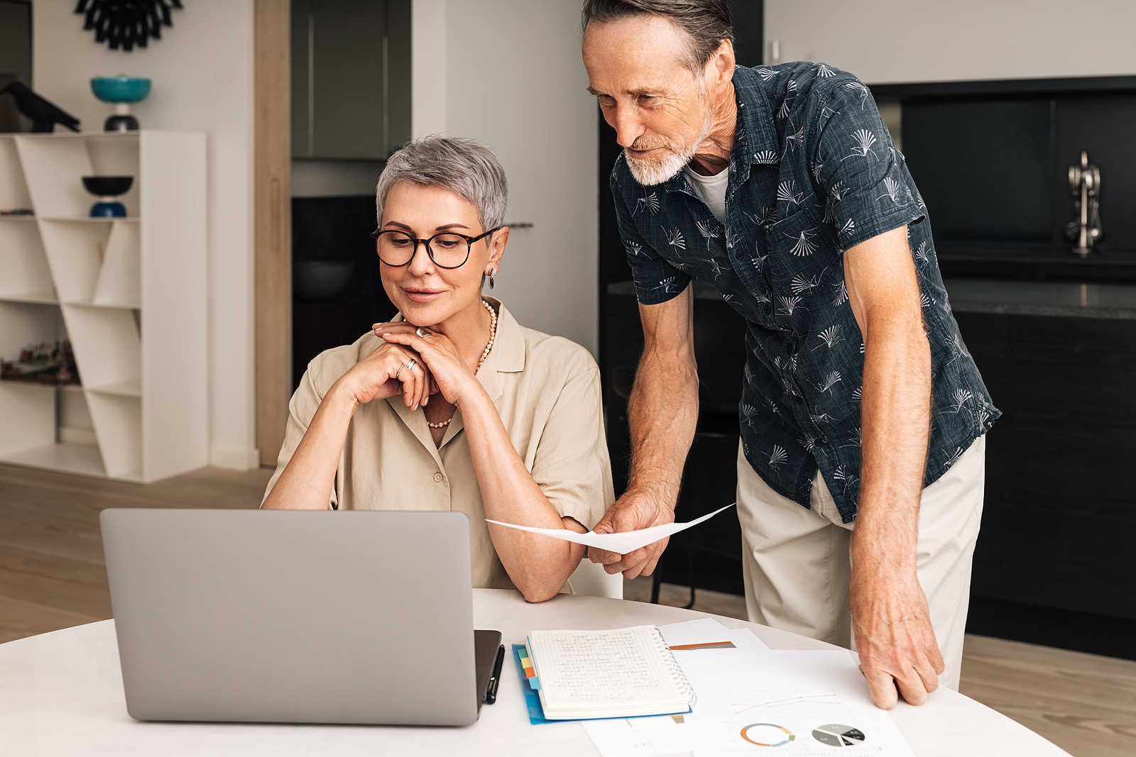 a man and woman look at their online bank and loan accounts together.