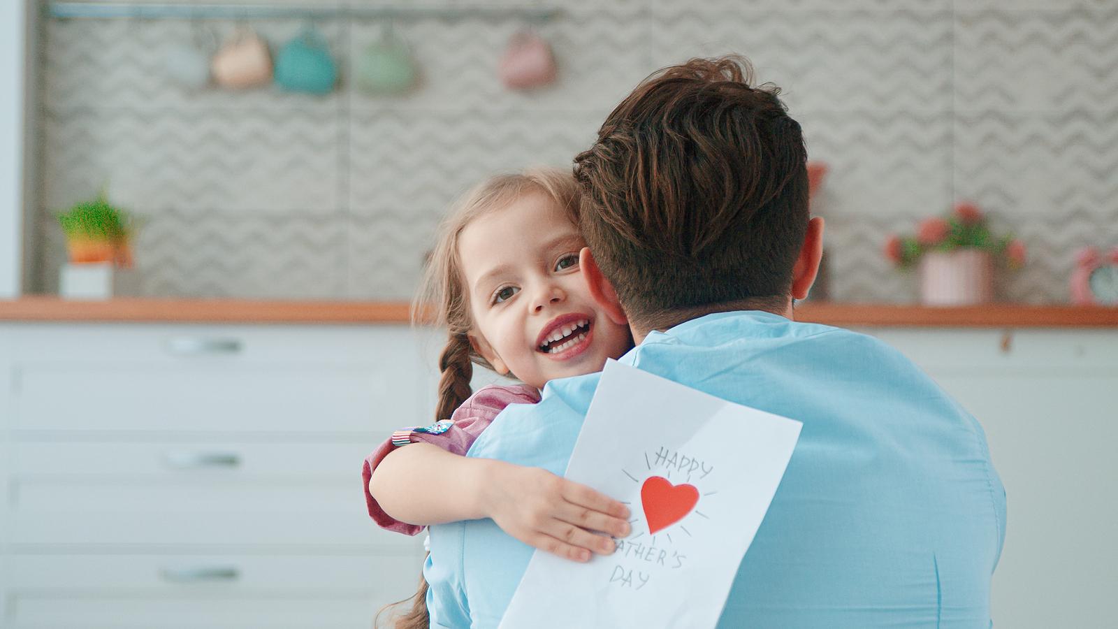 a blonde little girl hugs her dad.